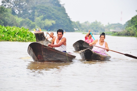 Local people row out from their flooded homes to receive some aid.