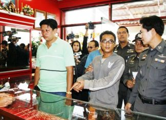 Bunliam Luechailam shows police and the press how he held up a gold shop.