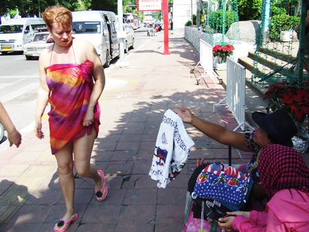Aunt Tun tries to sell her swimwear to passing tourists.