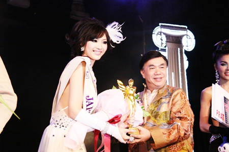 Ami Takeuchi from Japan receives the 1st runner up trophy from Pageant Chairman Dr. Seree Wongmontha.