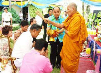 Phra Khru Visuthipiyakorn blesses General Kanit and Khunying Busyarat by sprinkling them with lustral water, calling on all that is sacred to give them good health and prosperity.