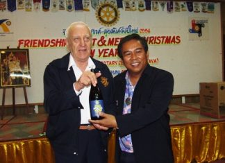 Noppadon Saengma, president of the Rotary Club of Pattaya presents Past Assistant Governor Dennis Stark the prize for most attendance, a unique bottle of 'Stop Polio Now' wine.