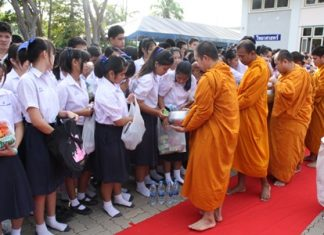 Singsamut students give alms to Buddhist monks at Sattahip Temple before presenting relief goods for flood victims to the Royal Thai Navy.