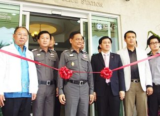 Officials prepare to cut the ribbon on the new police public-service booth.