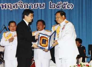 """Prime Minister Abhisit Vejjajiva (left) awards Vice Adm. Sommai Prakansamut (right), director-general of the Naval Education Department and one of the many the PM inducted into the Royal Thai Navy's """"hall of fame"""" for service above and beyond the call of duty."""