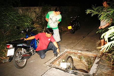Rescuers arrive and after checking over the victim, begin to hoist the motorbike out of the drain.