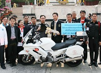 Mayor Itthiphol Kunplome (center right) hands over the symbolic keys to the new motorcycle to Pol. Col. Nanthawut Suwanla-Ong (center left).