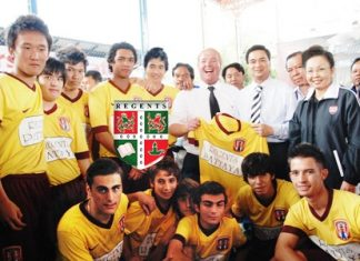Prime Minister Abhisit Vejjajiva, standing 4th right, receives a Regents School soccer jersey from Phil Larkin, standing 6th right, the coach of the Regents team.
