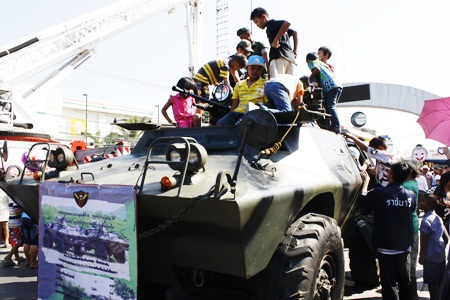 Children at Pattaya City Hall are given the chance to climb aboard a military vehicle.