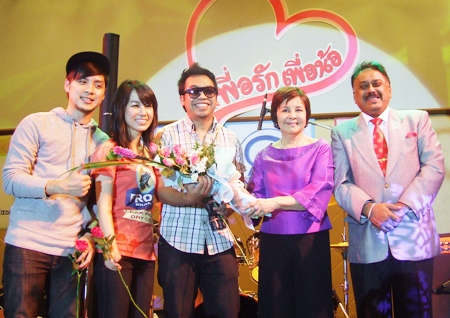 Sophin Thappajug and Peter Malhotra present a bouquet to the Room 39 Trio thanking them for their participation in the charity concert.