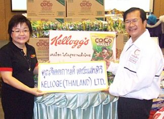 Jittakarn Taechasansiri (left), customer service manager for Kellogg's Thailand Co., presents Coco Balls cereal to Father Dr. Michael Pichan Jaiseri (right) president of the Father Ray Foundation.