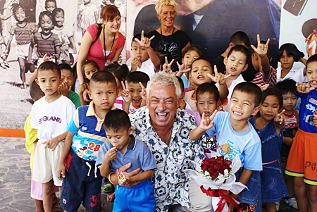 Danish singing legend Johny Reimer, center, a longtime supporter of the Pattaya Orphanage, enjoys a tremendous reception from the kids on his well received return visit.