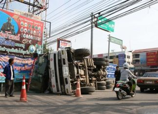 Driver Kan Kanhawong (left) stands next to the overturned cement truck he crashed in Sattahip.