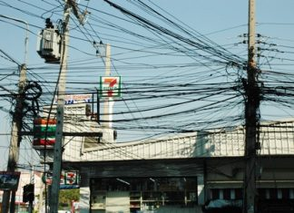 The tangled mess of electric and phones cables of different shapes and sizes hangs precariously above the road and sidewalks at the soi 17 intersection on Third Road.