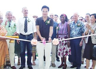 Prinn Panichpakdi from CLSA cuts the ribbon to officially open the new center, as supporters of the CPDC cheer him on.