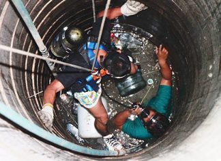 A rescue worker is lowered into the well to retrieve 15-year-old Kittipong.
