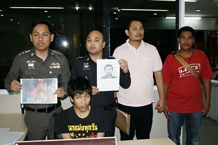 Police, shown here holding photos of two more suspects, have arrested Santhan Kammongkol (seated) for his involvement in the robbery of a 7-Eleven.