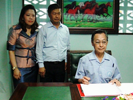 Former Prime Minister Chuan Leekpai signs the guestbook at the new Democrat Party headquarters in Chonburi.