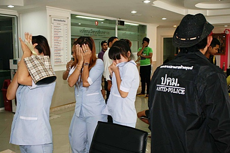 Staff at the clinic hide their faces as they are led away for questioning by the police.