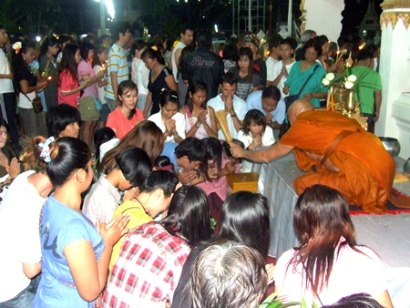 Buddhist devotees receive a blessing from a monk at Wat Chaimongkol in South Pattaya.