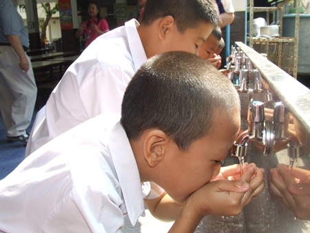 Children drink from the stainless steel trough where the water is obtained.