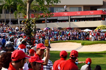 Huge crowds gather around the 18th green as the final pairing prepare to putt out.