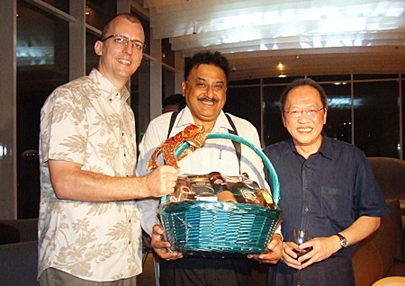 Harald Feurstein, GM of the Hilton Pattaya presents a gift to Peter as Chatchawal happily looks on.
