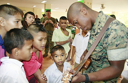 The children were impressed with this Marine's musical skills.
