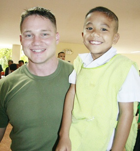 One of the bigger Marines poses with one of the Home's smallest boys.