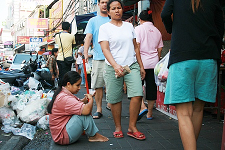 At South Pattaya's Wat Chaimongkol Market, vendors complain that child and disabled beggars operate with impunity, protected by moneyed criminals.