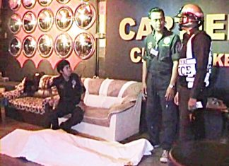 The body of Briton Anthony Rollins lies covered on the floor of the Cartier Karaoke as police wait to question staff members there.