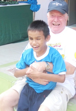 Erle and a young boy happily participate in the School for the Blind's Sports Day last month.
