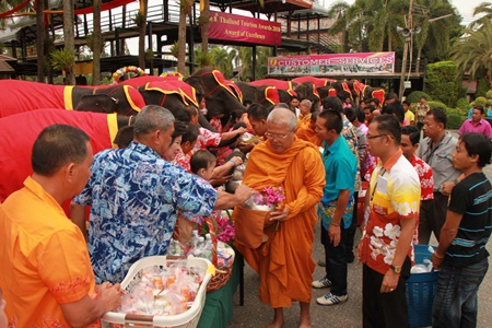 The tourist attraction's Songkran Festival began early April 13 with 19 elephants giving alms and dried foods to nine monks from area temples.