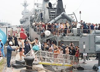Tourists disembark from the HTMS Sukhothai in Sattahip after being rescued from flood-ravaged resorts in Koh Tao and Koh Phangan. Royal Thai Navy ships rescued more than 800 tourists who had been stranded there during the recent foul weather.