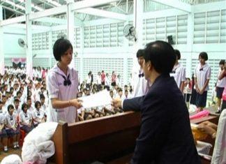 Principal Warakorn Ruenkamol hands out diplomas to 577 students at Banglamung School, Thursday, March 31.