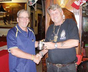 Peter Blackburn, left, receives his Cafe Kronborg April Monthly Mug from Bjarne Nielsen.