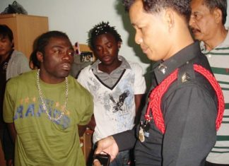 The two Cameroonian football players are arrested by police at their south Pattaya apartment.