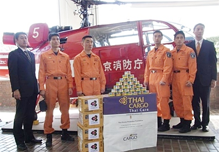 Chiriki Amaike (far left), THAI Cargo sales manager in Tokyo, and Senyo Ko (far right), THAI Cargo assistant sales manager in Tokyo, represented Thai Airways International Public Company Limited in receiving a shipment of 42 boxes of canned tuna recently. The tuna shipment, transported by THAI Cargo, was donated by the National Scout Association of Thailand and the Rover Scout Unit from Pathumwan Institute of Technology to assist rescue officials at the Fukushima nuclear power plant in Japan.