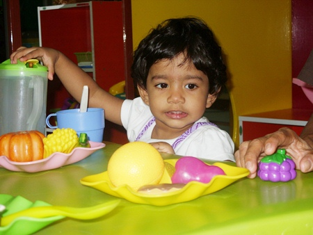 A youngster learns about food at the playgroup.
