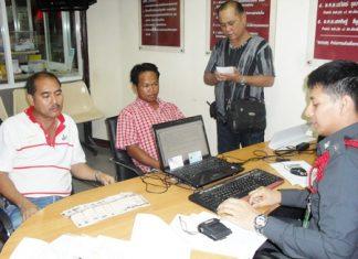 Somsak Satiplan and Veera Poonsuk turn the money over to police.