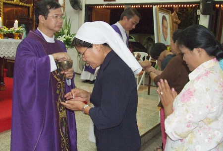 Fr. Picharn Jaisale performs the Eucharist during mass.