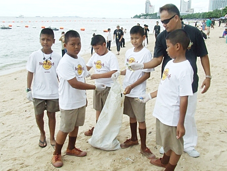 Youngsters and staff pick up trash off Pattaya Beach.