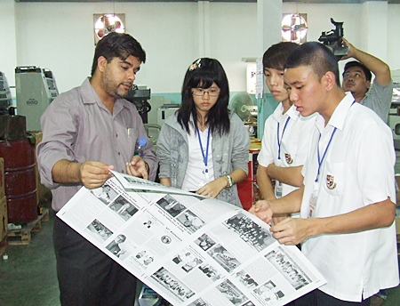 """(L to R) Suwanthep """"Tony"""" Malhotra and Ohmmy from Pattaya Mail show Minhyuk and Tammy from St Andrews how a newspaper is printed."""