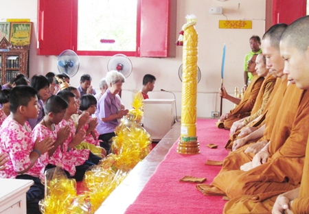 Teachers and students from the Redemptorist School for the Blind offer their Buddhist Lent Candle and necessities to local monks.