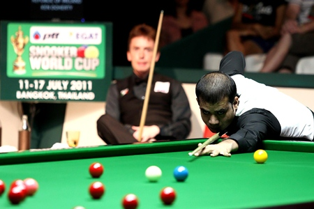 Former World Champion Ken Doherty of Ireland sits and watches as Pakistan's Muhammad Sajjad attempts to clear the table during their PTT-EGAT Snooker World Cup opening match in Bangkok, Monday, July 11.