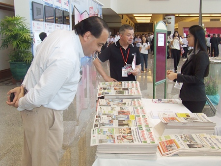 Guests pour over the latest edition of the Pattaya Mail at our booth during the expo.