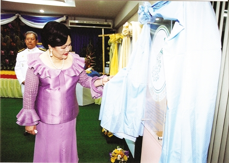 Her Majesty the Queen inspects some Royal silk on display for Her to give Her approval.