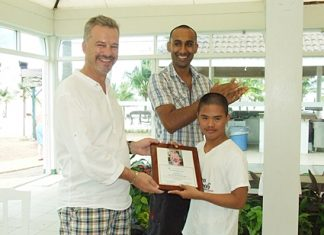 A boy presents Ingo Raeuber with a certificate of gratitude for making their day at the beach a most memorable one.