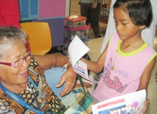 A youngster presents her grandmother with a hand made card for Mothers' Day.