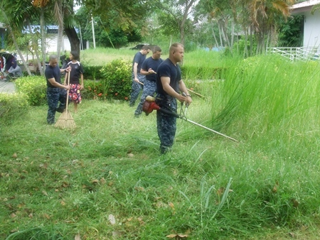 This is not an easy lawn to mow - sailors help tidy up the grounds at the Guranyawet Home for the Disabled in Banglamung.